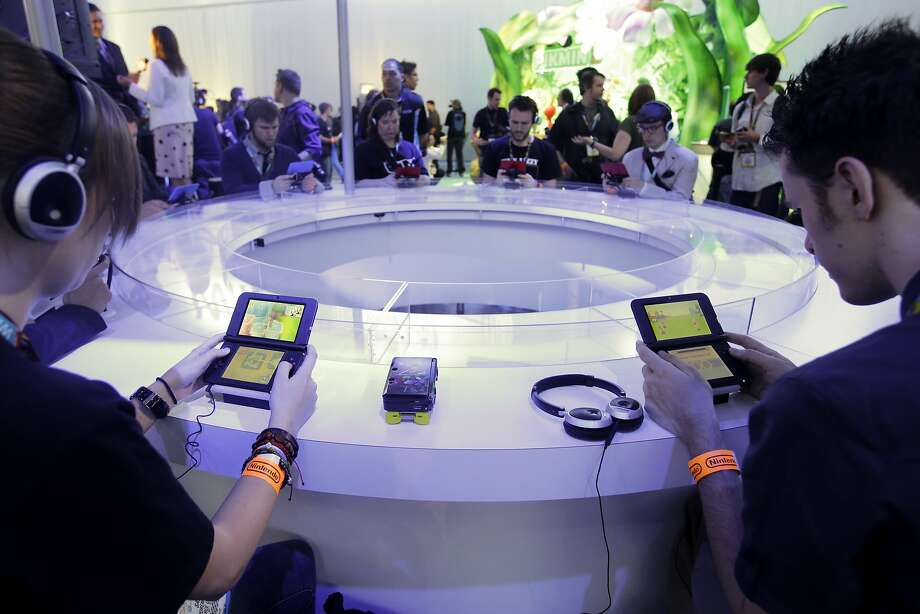 Attendees of the 2013 E3 game convention in Los Angeles play video games on the Nintendo 3DS. Photo: Jae C. Hong, Associated Press