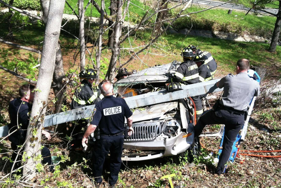 Fire and police personnel work to free a driver trapped in an SUV that left Interstate 95, between southbound Exits 22 and 21, Wednesday morning and tumbled down an embankment. Photo: Fairfield Fire Department / Fairfield Citizen
