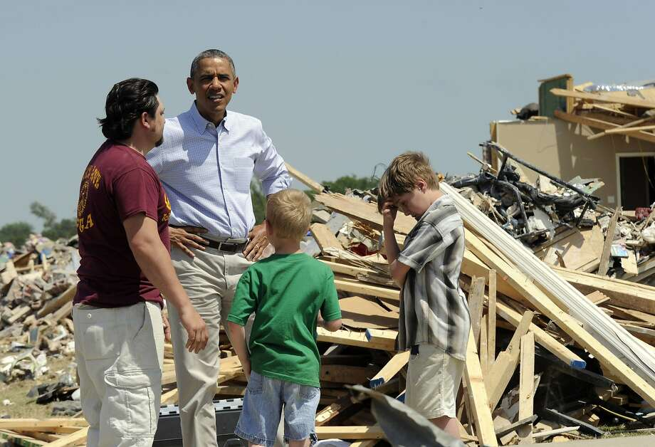 President Obama talks with Daniel Smith and his sons Garrison Dority and Gabriel Dority while touring part of Vilonia, Ark., which was ravaged by tornadoes last month. It was the first Arkansas visit of Obama's presidency. Photo: Susan Walsh, Associated Press