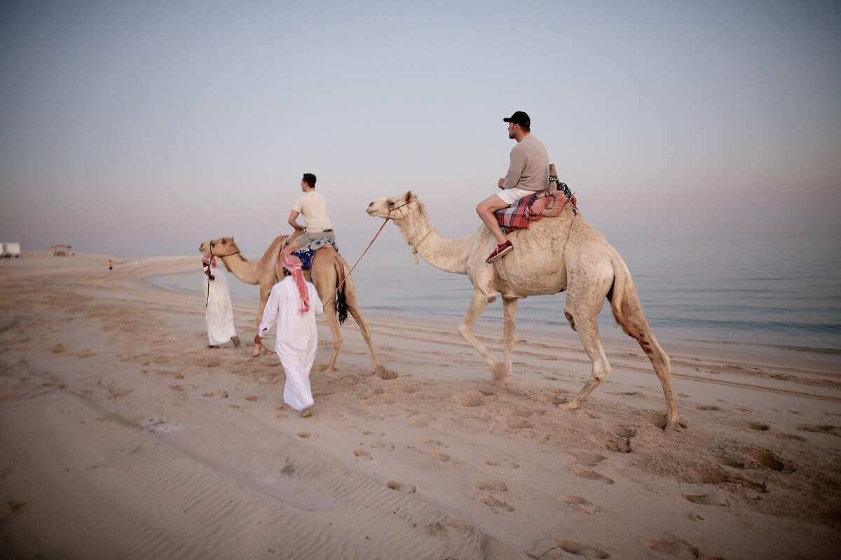 Richard III cast members Chandler Williams (left) and Kevin Spacey take a camel ride in the desert whilst on tour in Doha, Qatar, in,