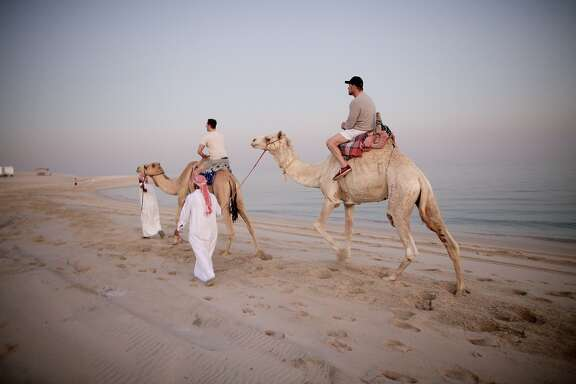 "Richard III cast members Chandler Williams (left) and Kevin Spacey take a camel ride in the desert whilst on tour in Doha, Qatar, in, ""Now: In the Wings on the World Stage."""