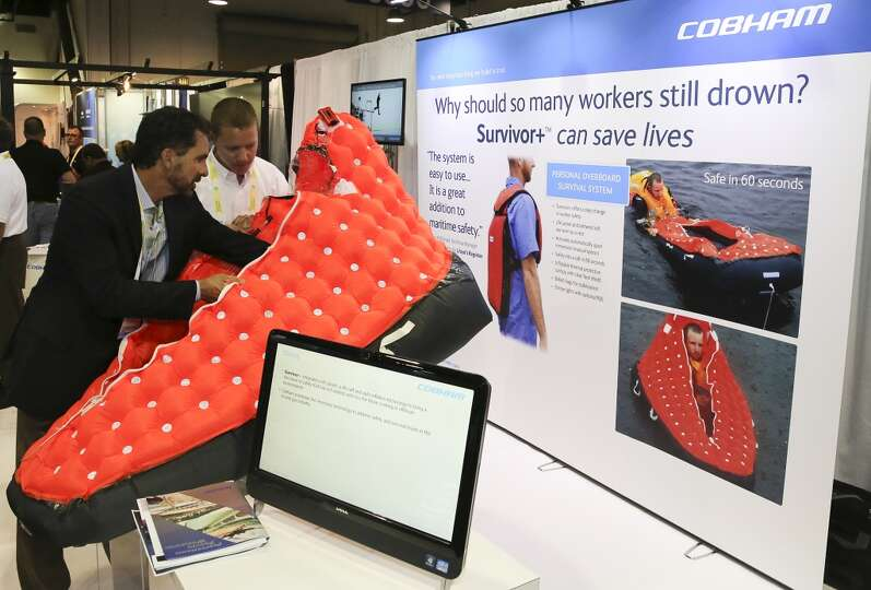 A Cobham employees displays to a customer how the Cobham personal overboard survival system works on