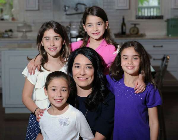 At center, Lori Woodring with her daughters, clockwise from lower left, Siena, 7, Tessa, 9, Lia, 5, and Isabella, 9, at their Old Greenwich home, Wednesday, May 7, 2014. Photo: Bob Luckey / Greenwich Time