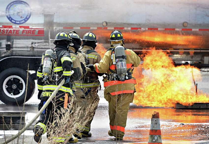 An instructor, right, leads firefighter trainees during a live fire training drill on best practices for the suppression of ignitable liquids such as crude oil in the event of a flammable liquid emergency at the Port of Albany Wednesday May 7, 2014, in Albany, NY. (John Carl D'Annibale / Times Union)