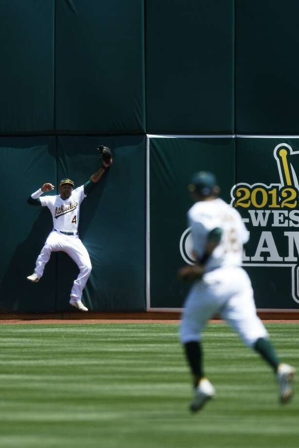 Coco Crisp makes a great catch on Kyle Seager's fourth-inning fly, but he left with a strained neck after crashing into the wall. Photo: Pete Kiehart, The Chronicle