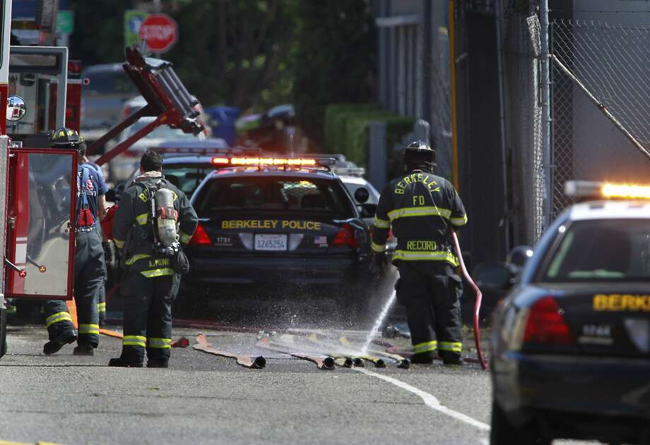 Firefighters clean equipment on Second Street after dousing a suspicious fire below the University Avenue overpass in Berkeley, Calif. on Wednesday, May 7, 2014. The cause of the blaze, which snarled traffic on the freeway and surface streets, is under investigation. Photo: Paul Chinn, The Chronicle