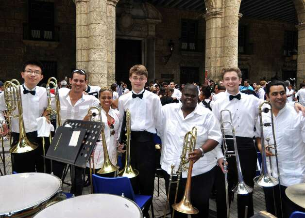 The Greenwich High School wind ensemble's trombone section gathers with the trombone section of the National Band of Cuba after the two groups' combined performance in April 2014. The GHS students, in bow ties, left to right, are Aaron Kim, Paul Collins and Ben Albano. Photo: Picasa, Contributed Photo / Greenwich Time Contributed