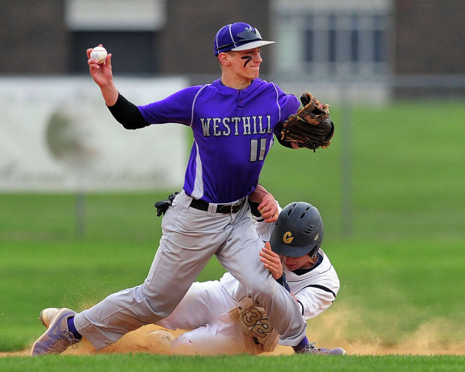 Westhill's John Spoto throws to first as Trumbull's Carlos Garrido slides into second, during baseball action in Trumbull, Conn. on Wednesday May 7, 2014. Photo: Christian Abraham / Connecticut Post