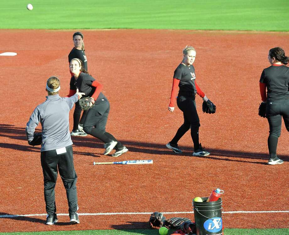 Lamar head coach Holly Bruder, left, tosses pop-up balls to some of her outfielders as they get in some practice on the dry infield of Vincent-Beck Stadium in 2012. The Lady Cardinals will play home games next season on a on-campus field. The past two season, Lamar had played home games at Ford Park. Enterprise file photo Photo: Dave Ryan