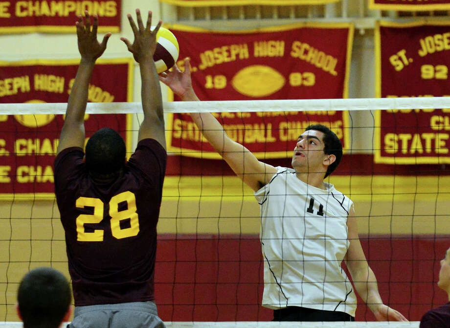 Ridgefield'sGriffin Jones, right, tries to get the ball past St. Joseph's Erick Langston, during volleyball action in Trumbull, Conn. on Wednesday May 7, 2014. Photo: Christian Abraham / Connecticut Post