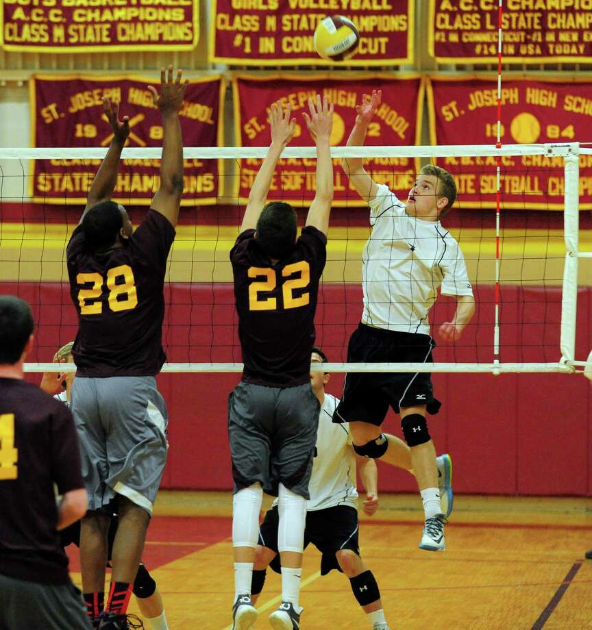 Ridgefield's Karl Liapunov, right, tries to get the ball past St. Joseph's Erick Langston, left, and Marc Mrozek, during volleyball action in Trumbull, Conn. on Wednesday May 7, 2014. Photo: Christian Abraham / Connecticut Post