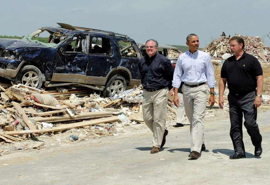 En route to California, President Barack Obama tours tornado-damaged Vilonia, Ark., Wednesday with Sen. Mark Pryor, D-Ark., left, and the town's mayor, James Firestone. The president also met with residents affected by the storms. Photo: Susan Walsh, STF / AP
