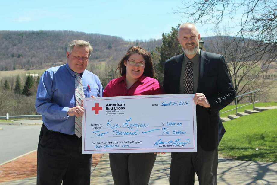 Red Cross Senior Account Manager Steve Leary, left, and SUNY Cobleskill Student Life Center Director Jeff Foote present a scholarship to sophomore Kia Lamica for her leadership of campus-wide blood drives. (SUNY Cobleskill)