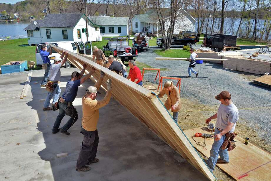 Capital Region Builders and Remodelers Association and Community Partners volunteers erect new cabins at Camp Scully on Snyder's Lake Wednesday May 7, 2014, in Wynantskill, NY.  (John Carl D'Annibale / Times Union) Photo: John Carl D'Annibale / 00026749A