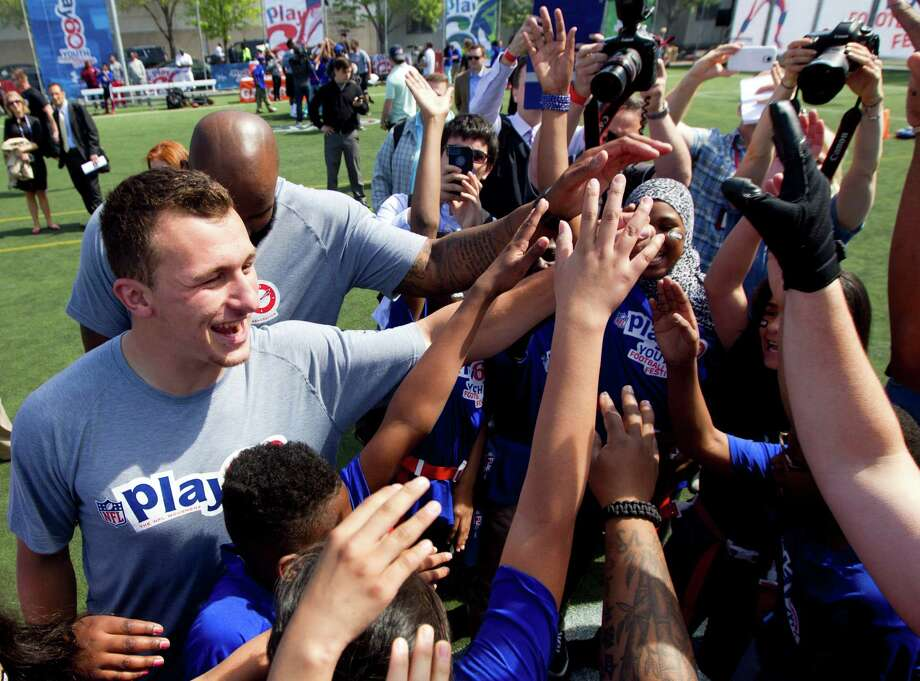 On May 7, 2014, at New York's Chelsea Waterside Park, Johnny Manziel, left, was among draft prospects taking part in an NFL clinic with 80 kids, many impacted by a recent gas explosion in their Harlem community. Photo: Brett Coomer, Staff / © 2014 Houston Chronicle