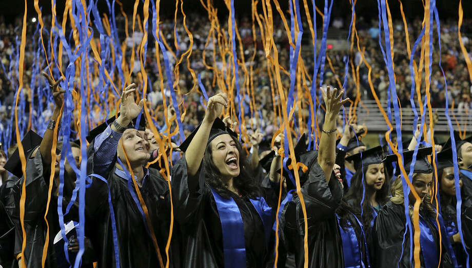 University of Texas at San Antonio graduate Manal Foty (center) and others cheer during UTSA's 2013 graduation ceremonies. Some 4,450 are eligible to walk the stage in this year's graduation rites Saturday at the Alamodome. Photo: San Antonio Express-News / © 2013 San Antonio Express-News