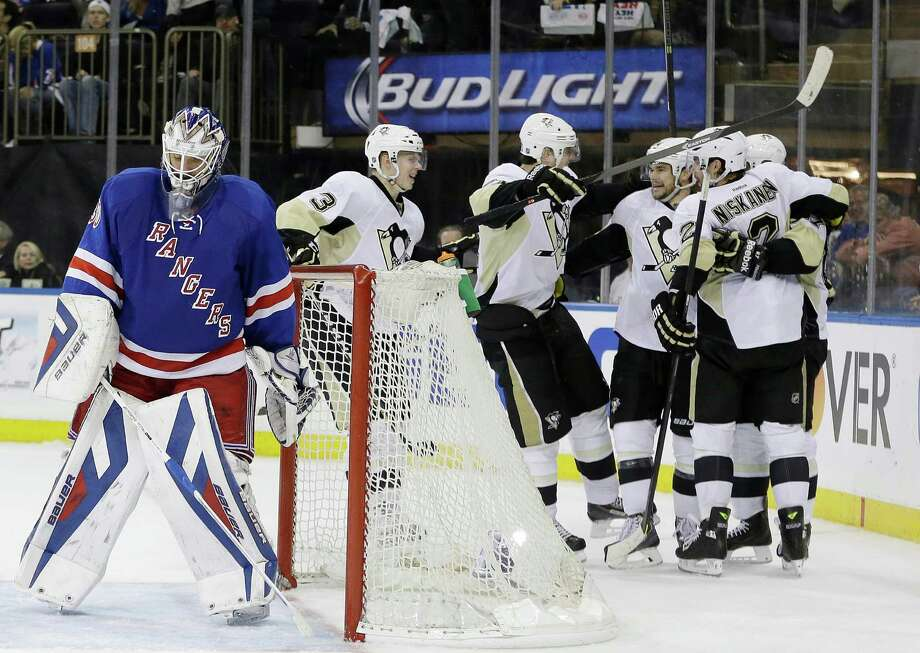 New York Rangers goalie Henrik Lundqvist, left, of Sweden, reacts as the Pittsburgh Penguins celebrate a goal by Chris Kunitz during the third period of a second-round NHL Stanley Cup hockey playoff series Wednesday, May 7, 2014, in New York. The Penguins won 4-2. (AP Photo/Frank Franklin II) ORG XMIT: MSG115 Photo: Frank Franklin II / AP