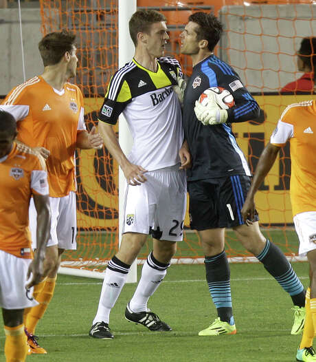Dynamo goalkeeper Tally Hall, right, gives the Crew's Adam Bedell an earful during the second half Wednesday night. Hall made six saves in his shutout. Photo: J. Patric Schneider, Freelance / © 2014 Houston Chronicle