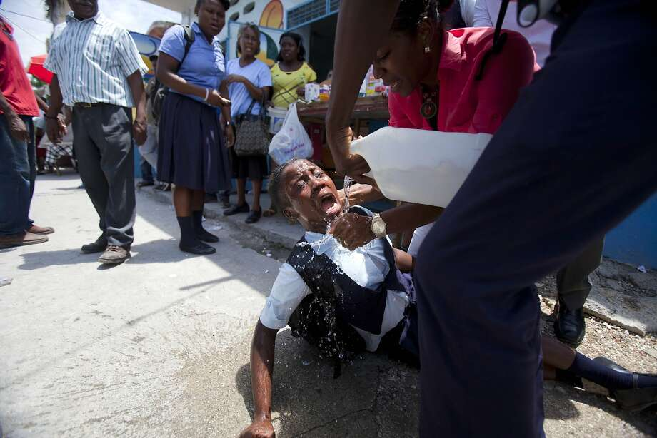 A student affected by tear gas is helped during clashes between students and the national police in Port-au-Prince, Haiti, Wednesday, May 7, 2014. Students are protesting to demand authorities respond to their striking teachers' demands for higher pay and improved working conditions. Students are concerned they will not be able to take exams which allow them to move on to the next level. Public school teachers across Haiti have been on strike for one week. (AP Photo/Dieu Nalio Chery) Photo: Dieu Nalio Chery, Associated Press