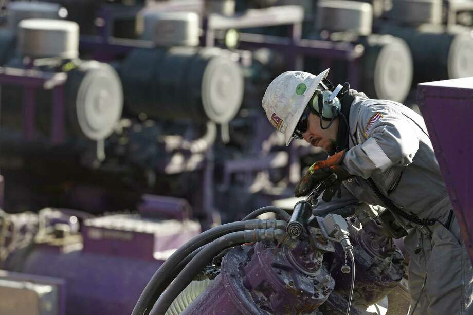 A worker oils a pump during a hydraulic fracturing operation at an Encana well pad near Mead, Colo. Encana Corp. unit Encana Oil & Gas will spend $3.1 billion on land in the Eagle Ford Shale that's rich in oil. Photo: Brennan Linsley, STF / AP