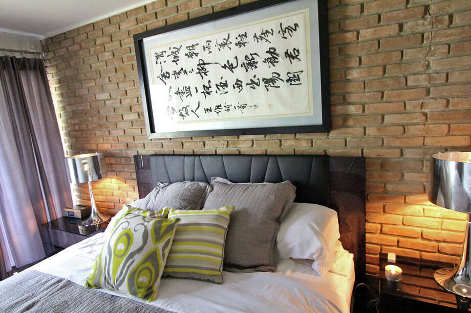 Marlon Quinones hung an Asian artwork horizontally rather than vertically over the bed because it fit and he liked the way it looked. Quinones bought the piece about friendship in Toronto. Photo: DANNY WARNER, For The Express-News / ALL RIGHTS RESERVED UNLESS OTHERWISE SPECIFIED