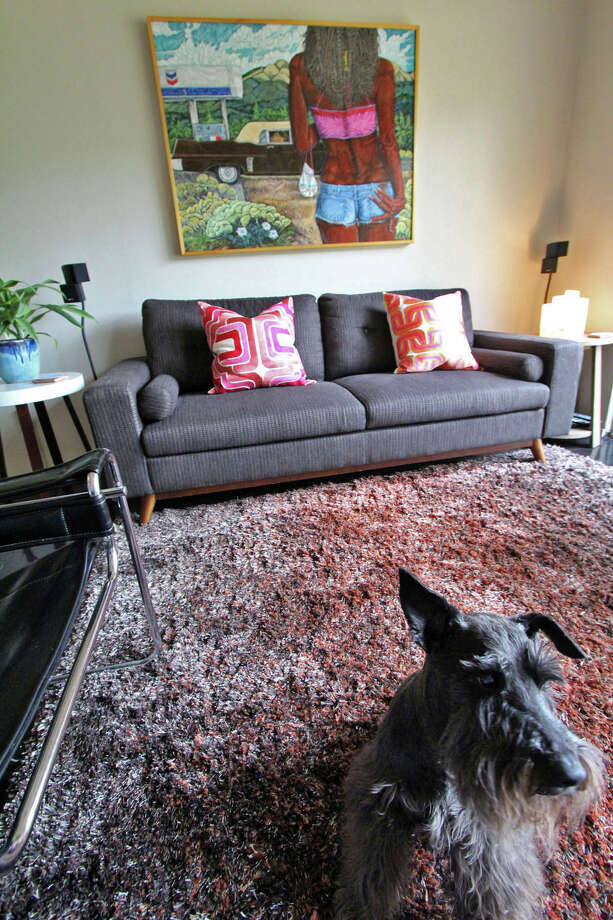 Marlon Quinones' and Hagan Retzloff's dog, Bentley, in the den. Above the sofa, ÒNadine,Ó a painting by New Mexico artist Henry Berger depicts the lyrics from the Chuck Berry song about Nadine walking toward a coffee-colored Cadillac. Photo: DANNY WARNER, For The Express-News / ALL RIGHTS RESERVED UNLESS OTHERWISE SPECIFIED
