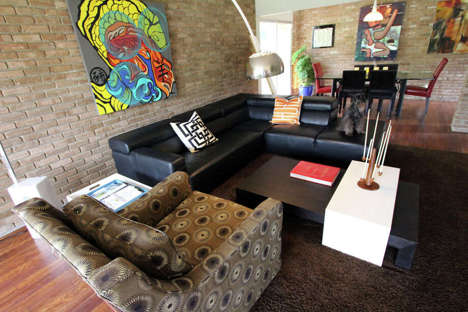 In the home of Marlon Quinones and Hagan Retzloff, a large contemporary painting hangs above the sofa in the living room, where Bentley the dog is perched. The sofa and Arco lamp came from Copenhagen; the black and white table was bought at Nest. Photo: DANNY WARNER, For The Express-News / ALL RIGHTS RESERVED UNLESS OTHERWISE SPECIFIED