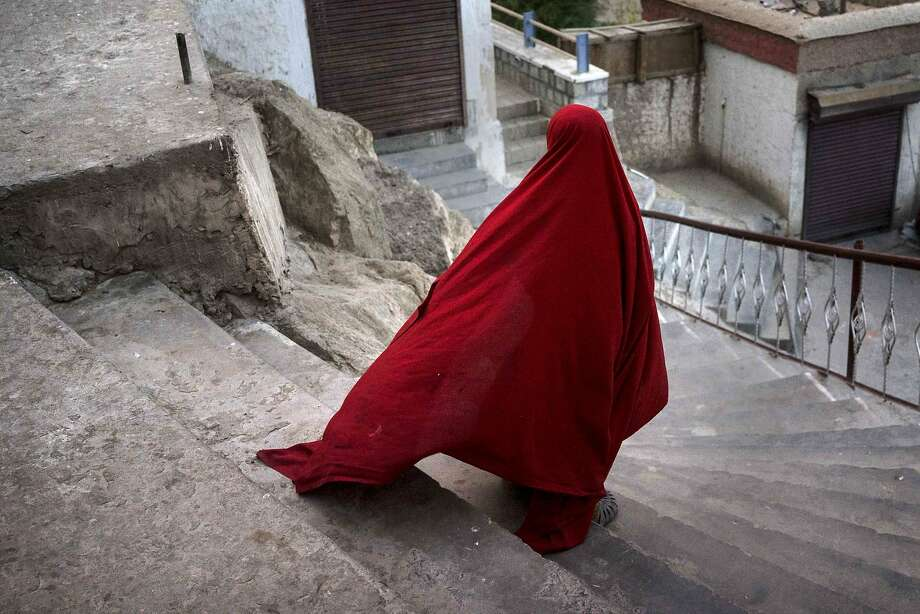 A young noviceBuddhist monk leaves the Thiksey Monastery after dinner in Thiksey, India. Photo: Kevin Frayer, Getty Images