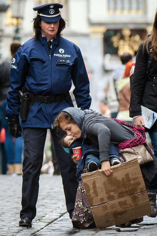 Brussels roust: A police officer removes a woman and child who were begging for money at 