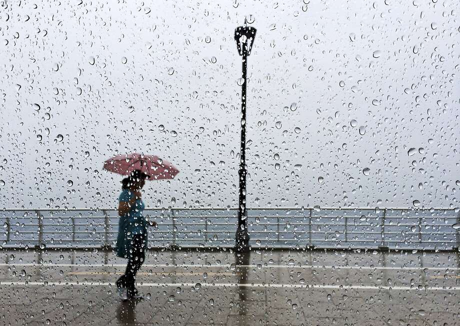Umbrella weather in the Mideast: A Lebanese woman walks in the rain on the Corniche, or 