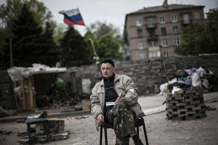 Taking a break from fomenting rebellion,a pro-Russia militant catches up on his reading 