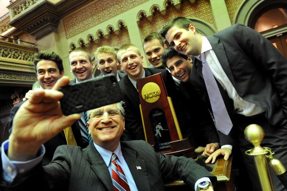 Assemblyman Jim Tedisco, center, takes a selfie with members of the Union hockey team and their NCAA Championship trophy in the Assembly Chambers on Wednesday, May 7, 2014, at the Capitol in Albany, N.Y. The hockey players, from left, are Sam Coatta, Matt Wilkins, Mark Bennett, Matt Krug, Charlie Vasaturo, Alex Sakellaropoulos and Dillon Pieri. (Cindy Schultz / Times Union) Photo: Albany Times Union