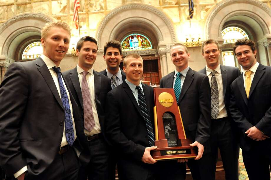 Union hockey players pose with their NCAA Championship trophy in the Senate Chambers on Wednesday, May 7, 2014, at the Capitol in Albany, N.Y. From left, are Mark Bennett, Dillon Pieri, Alex Sakellaropoulos, Matt Wilkins, Matt Krug, Charlie Vasaturo, and Sam Coatta. (Cindy Schultz / Times Union) Photo: Albany Times Union