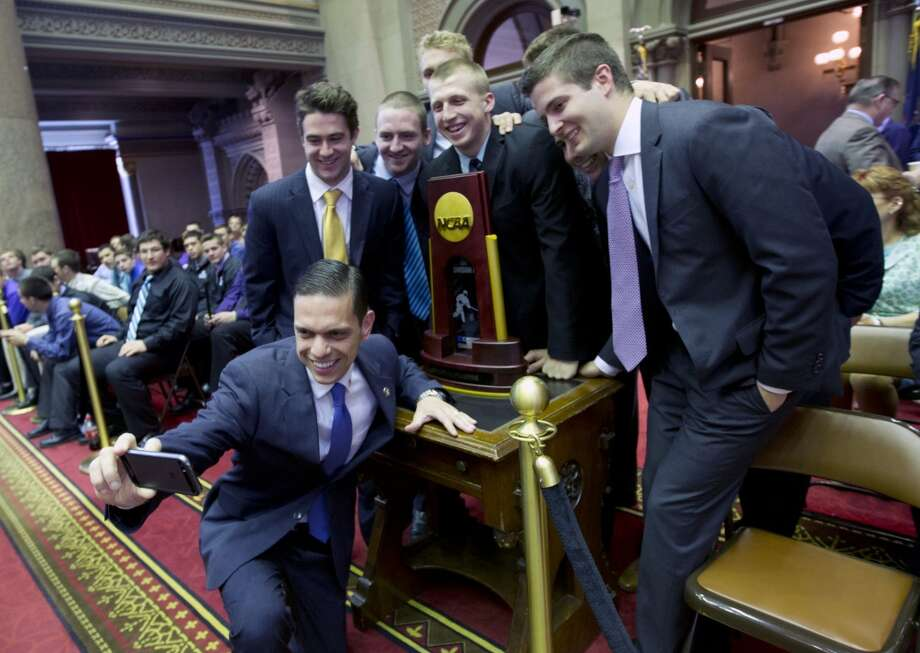 Assemblyman Angelo Santabarbara, D-Schenectady, takes a photo with members of the Union College hockey team in the Assembly Chamber at the Capitol on Wednesday, May 7, 2014, in Albany, N.Y. The team was honored for winning the NCAA college hockey championship. (AP Photo/Mike Groll) ORG XMIT: NYMG103 Photo: AP