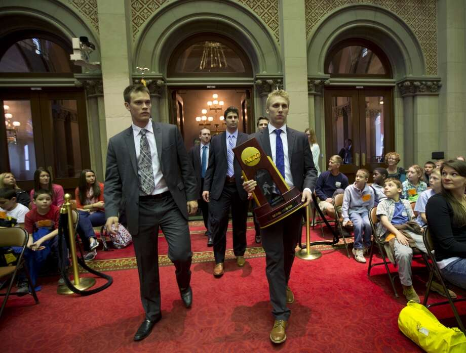 Union College hockey players Charlie Vasaturo, left, and Mark Bennett, carrying the NCAA college hockey championship trophy, walk into the Assembly Chamber at the Capitol with other team members on Wednesday, May 7, 2014, in Albany, N.Y. The team was honored for winning the championship. (AP Photo/Mike Groll) ORG XMIT: NYMG102 Photo: AP