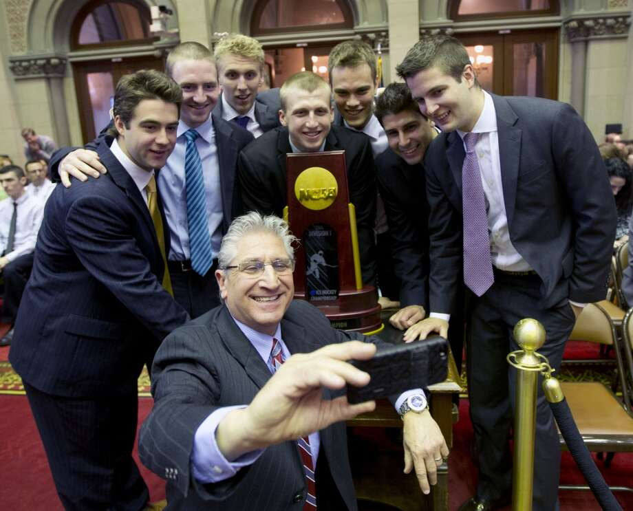 Assemblyman James Tedisco, R-Clifton Park, takes a photo with members of the Union College hockey team before the team was honored for winning the NCAA college hockey championship in the Assembly Chamber at the Capitol on Wednesday, May 7, 2014, in Albany, N.Y. Tedisco is a Union alumn. Team members, from left, are Sam Coatta, Matt Wilkins, Mark Bennett, Matt Krug, Charlie Vasaturo, Alex Sakellaropoulos and Dillon Pieri. (AP Photo/Mike Groll) ORG XMIT: NYMG101 Photo: AP