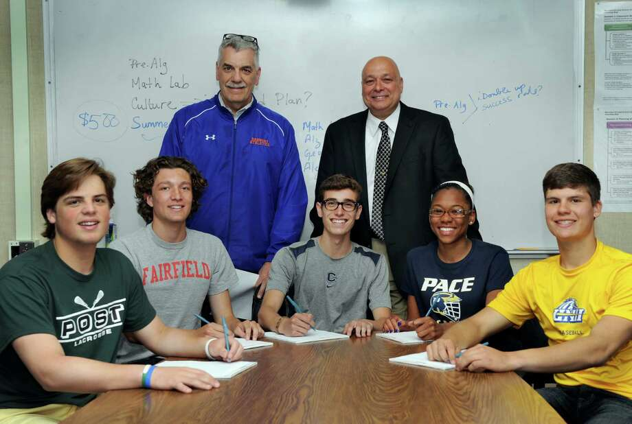Danbury High School Athletic Director Chip Salvestrini, left, and school Principal Gary Bocaccio, stand with five students athletes who have signed National Letters of Intent to play their sports in college Thursday, May 8, 2014. They are from left, Kevin Keiser, 17, Mickey Kozak, 18, Chazz Winter, 17, Najmah James, 17 and Mike Schweitzer, 17. Photo: Carol Kaliff / The News-Times