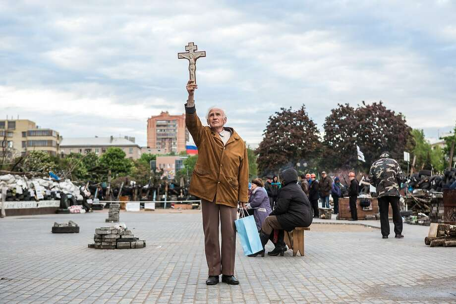 A man representing Orthodox Christians holds a cross by the office of pro-Russia activists in Donetsk. Photo: Brendan Hoffman, Getty Images