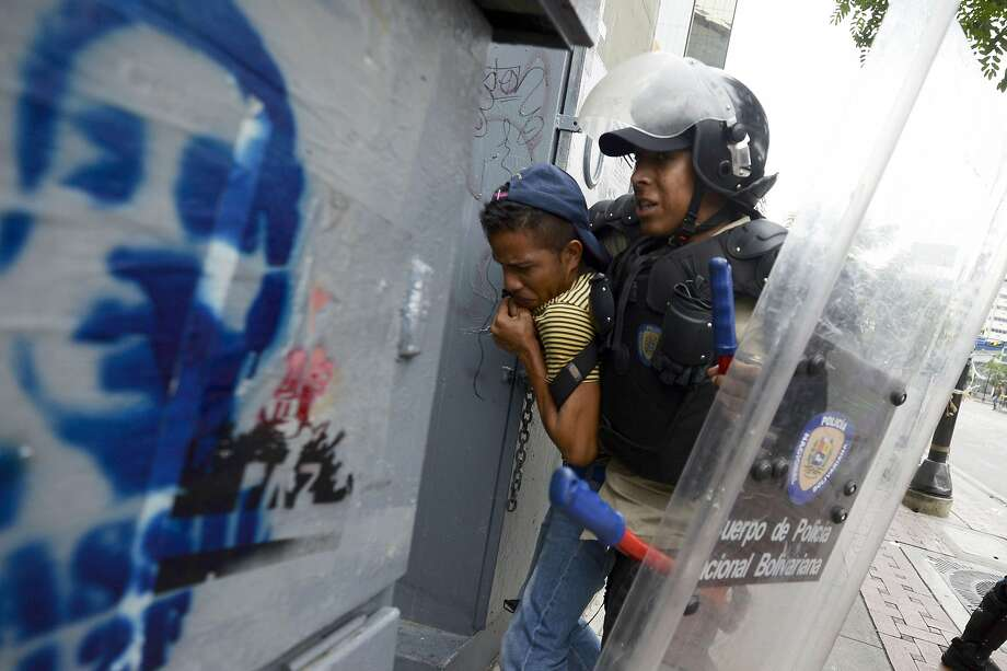 A riot policeman arrests a student taking part in an antigovernment protest in Caracas. Photo: Juan Barreto, AFP/Getty Images
