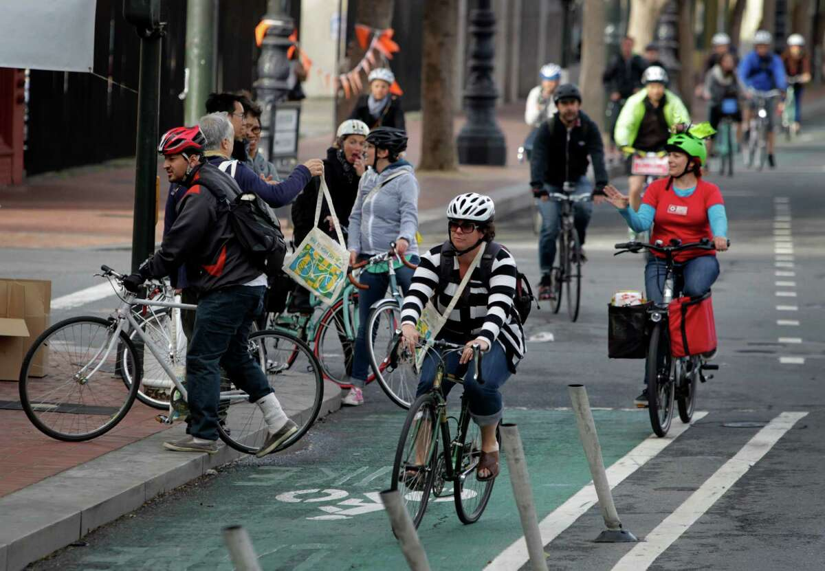 Bicyclists ride past an energizer station on Market and 12th streets for the 20th annual Bike to Work day in San Francisco on Thursday, May 8, 2014.