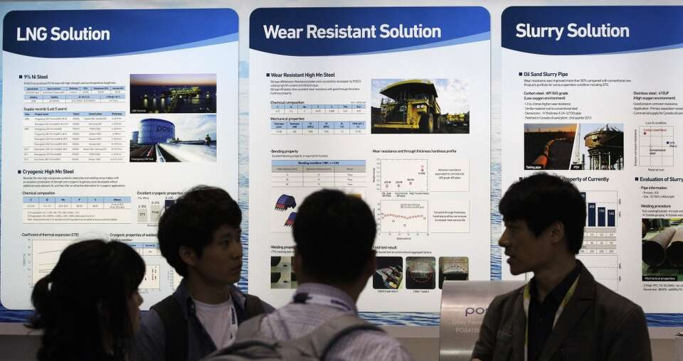 Exhibitors talk at the Global Posco booth located in the NRG Arena  during the Offshore Technology C