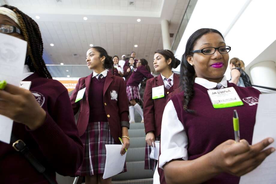 Jasmina Thomas, right, a Young Women's College Preparatory Academy student revises a list of questions as she and her classmates take the escalators to the conference exhibition floor as part of the High School STEM event, Thursday, May 8, 2014, in Houston. ( Marie D. De Jesus / Houston Chronicle ) Photo: Marie D. De Jesus, Houston Chronicle