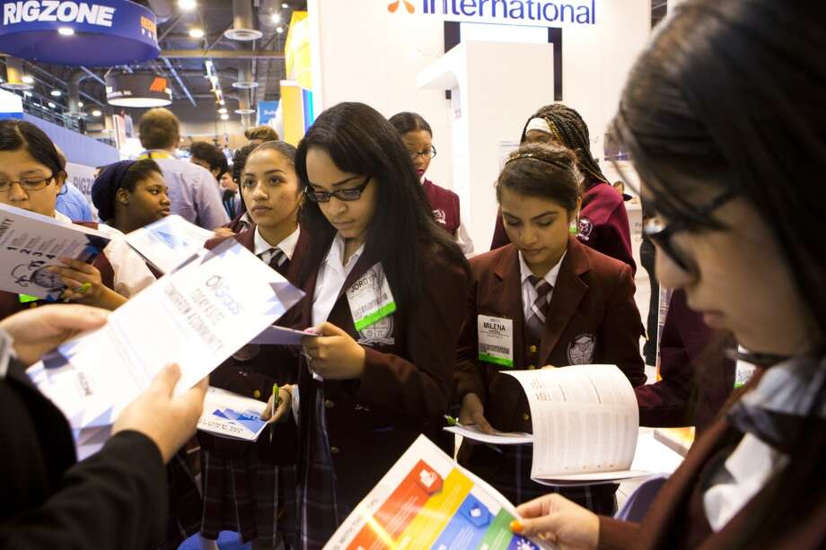 Jordyn Crawford, center, 15, a Young Women's College Preparatory Academy student receives a paperwork packet from the recruiter at the Rigzone booth during the Offshore Technology Conference, Thursday, May 8, 2014, in Houston. ( Marie D. De Jesus / Houston Chronicle ) Photo: Marie D. De Jesus, Houston Chronicle