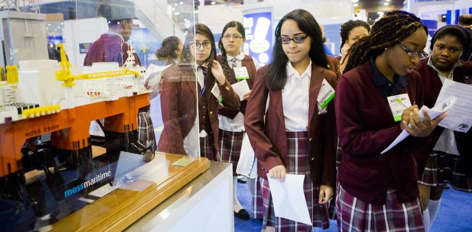 Young Women's College Preparatory Academy students walk by a miniature rig model as they take a tour