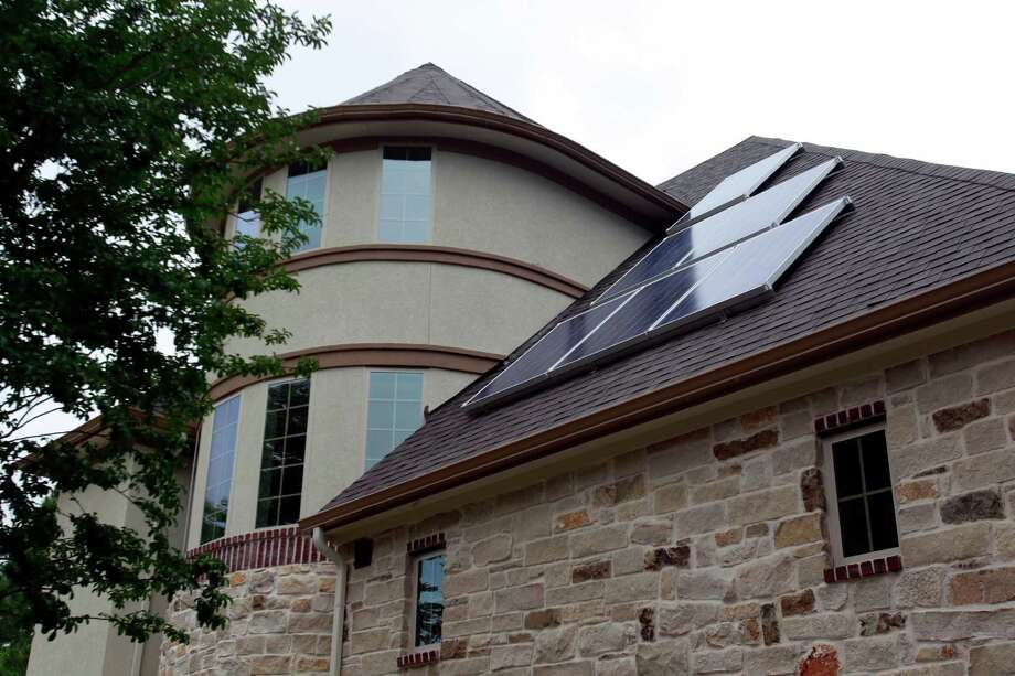 "Roof-mounted solar panels are part of the ""micro-trigeneration system"" that's designed to let the owners of this new four-bedroom, five-bath home in the Energy Corridor area to operate on or off the grid. Photo: Melissa Phillip, Staff / © 2014  Houston Chronicle"