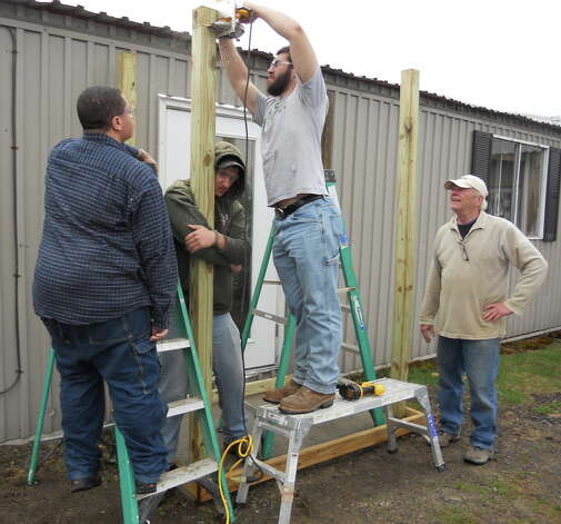 Questar seniors and construction interns Hasan Seabrook, Mike Jennings and Wyatt Beaumont of Greenville build a roof over Columbia County Habitat's office door during an internship last month. Habitat volunteer Ron Tanner, pictured right, supervised the students. (Submitted)