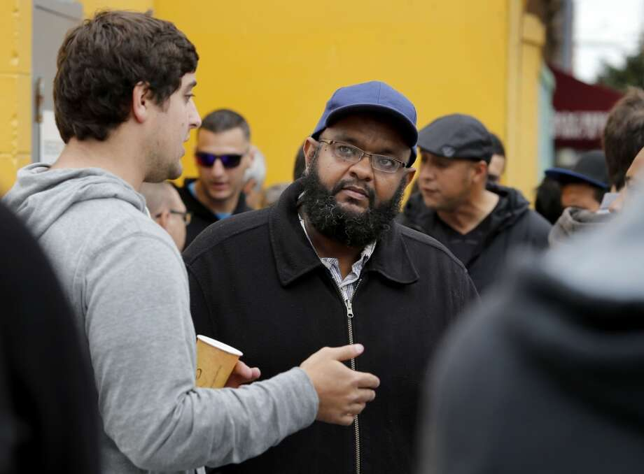 Uber official Brian Tolkin (left) tried to explain the reasons for the rate hikes to driver Zen Mohamed (center) during the rally and strike. Photo: Brant Ward, The Chronicle