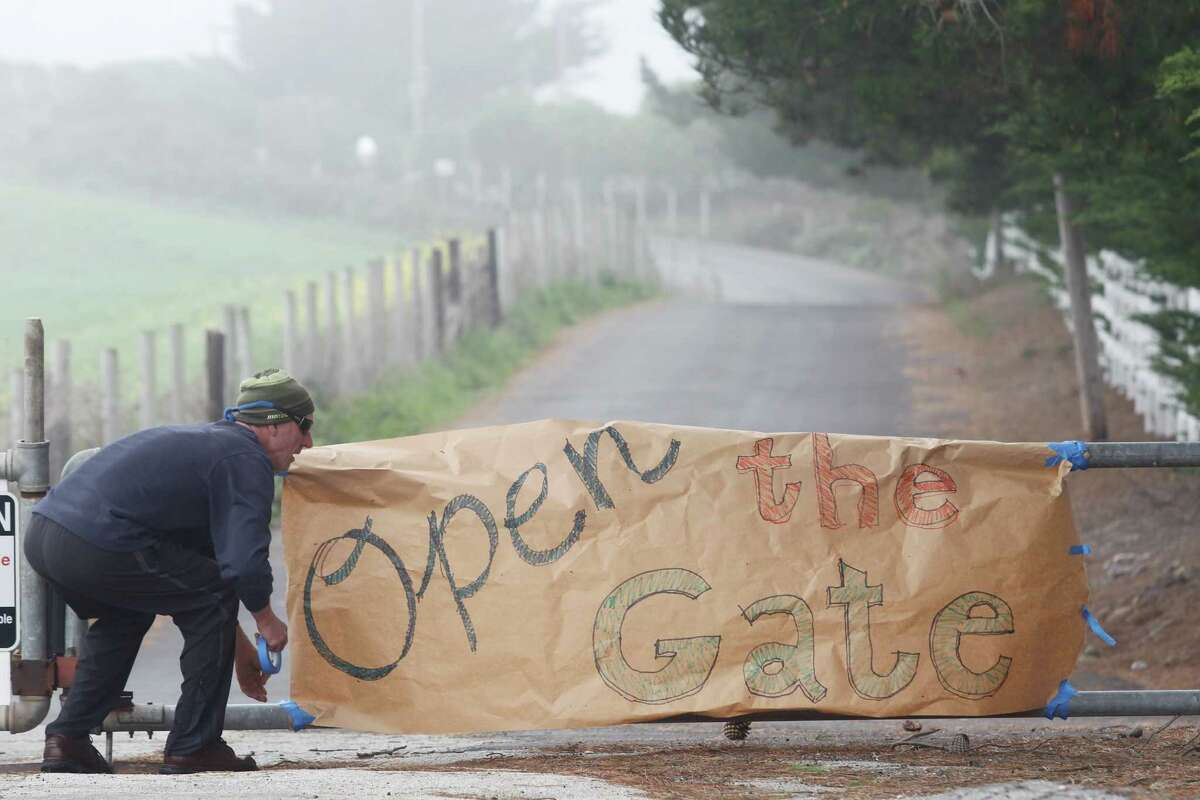 Protester Tom Wilhelm puts a sign on the gate at Martins Beach Road in March.