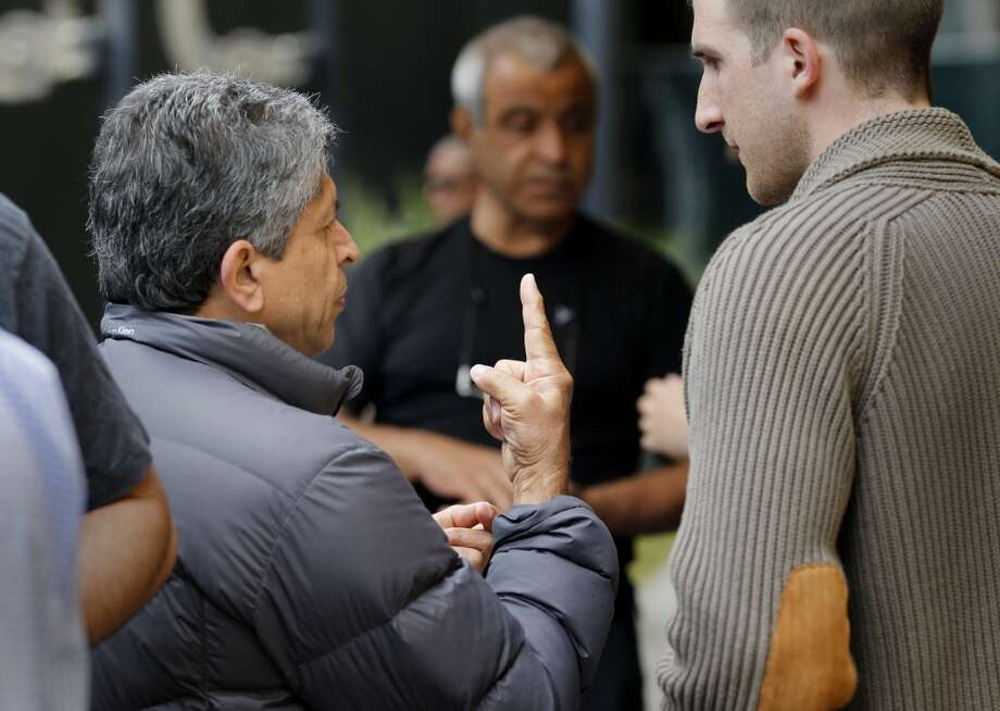 A driver who identified himself as Ferydon (left) made a point to a member of the Uber staff Thursday in San Francisco. UberX drivers, upset that the company is raising the commission it takes on their rides to 20 percent and charging a new phone fee, rallied near the company headquarters on Mission Street. Photo: Brant Ward, The Chronicle