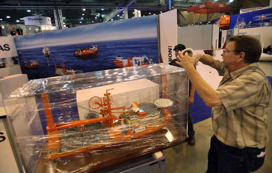 Richard Coleman wraps and protect a model ship, made by Coleman & Associates, as the tear down process begins upon the conclusion of the Offshore Technology Conference at NRG on May 8, 2014, in Houston Tx. ( Mayra Beltran / Houston Chronicle ) Photo: Mayra Beltran, Houston Chronicle